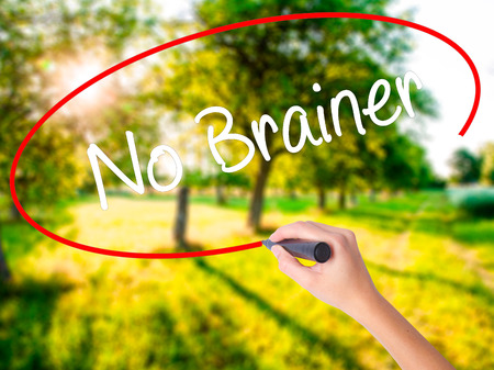 Woman Hand Writing No Brainer on blank transparent board with a marker isolated over green field background. Business concept. Stock Photo