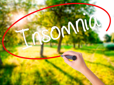 Woman Hand Writing Insomnia  on blank transparent board with a marker isolated over green field background. Stock Photo Stock Photo