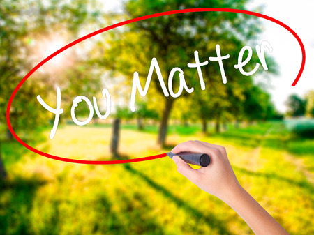 business matter: Woman Hand Writing You Matter on blank transparent board with a marker isolated over green field background. Business concept. Stock Photo