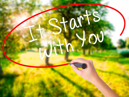 living wisdom: Woman Hand Writing It Starts With You on blank transparent board with a marker isolated over green field background. Business concept. Stock Photo Stock Photo
