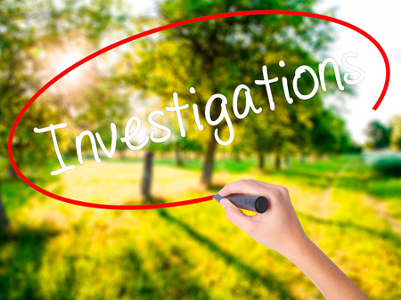 Woman Hand Writing Investigations  on blank transparent board with a marker isolated over green field background. Stock Photo