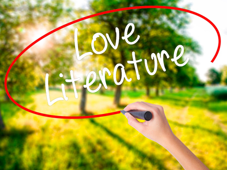 Woman Hand Writing Love Literature on blank transparent board with a marker isolated over green field background. Stock Photo Stock Photo