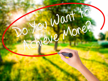 Woman Hand Writing Do You Want to Achieve More? on blank transparent board with a marker isolated over green field background. Business concept. Stock Photo