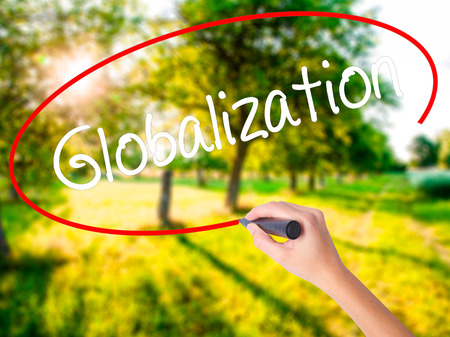 Woman Hand Writing Globalization on blank transparent board with a marker isolated over green field background. Stock Photo