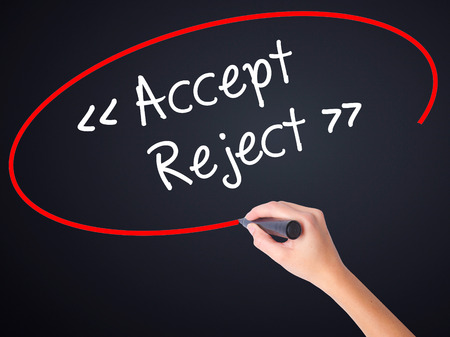 approvement: Woman Hand Writing Accept - Reject  on blank transparent board with a marker isolated over black background. Stock Photo
