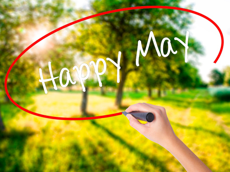 Woman Hand Writing Happy May on blank transparent board with a marker isolated over green field background. Business concept. Stock Photo