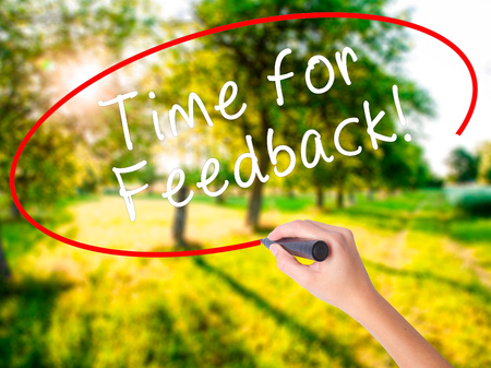 opinions: Woman Hand Writing Time for Feedback on blank transparent board with a marker isolated over green field background. Business concept. Stock Photo