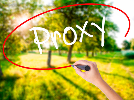 Woman Hand Writing Proxy on blank transparent board with a marker isolated over green field background. Stock Photo
