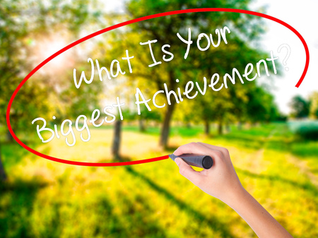 overachieving: Woman Hand Writing What Is Your Biggest Achievement? on blank transparent board with a marker isolated over green field background. Stock Photo Stock Photo