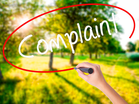 unacceptable: Woman Hand Writing Complaint on blank transparent board with a marker isolated over green field background. Business concept. Stock Photo