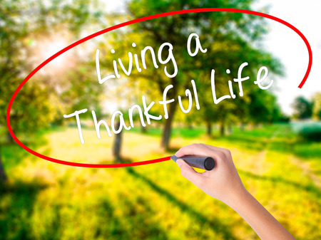 humility: Woman Hand Writing Living a Thankful Life on blank transparent board with a marker isolated over green field background. Business concept. Stock Photo