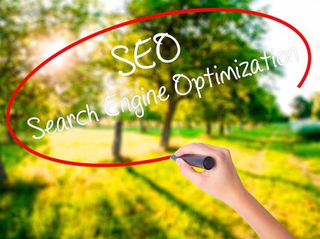 Woman Hand Writing SEO Search Engine Optimization on blank transparent board with a marker isolated over green field background. Business concept. Stock Photo