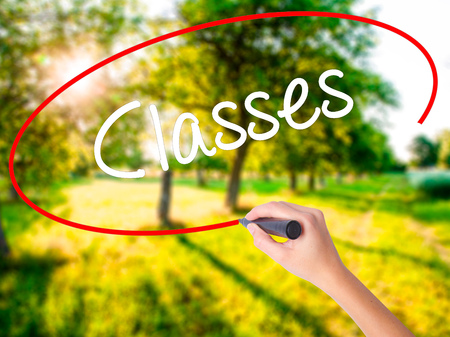 online degree: Woman Hand Writing Classes   on blank transparent board with a marker isolated over green field background. Business concept. Stock Photo