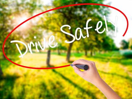Woman Hand Writing  Drive Safely on blank transparent board with a marker isolated over green field background. Business concept. Stock Photo