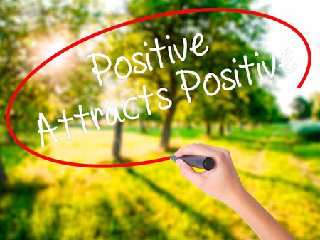 attracts: Woman Hand Writing Positive Attracts Positive on blank transparent board with a marker isolated over green field background. Stock Photo