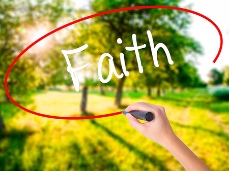 Woman Hand Writing Faith on blank transparent board with a marker isolated over green field background. Business concept. Stock Photo