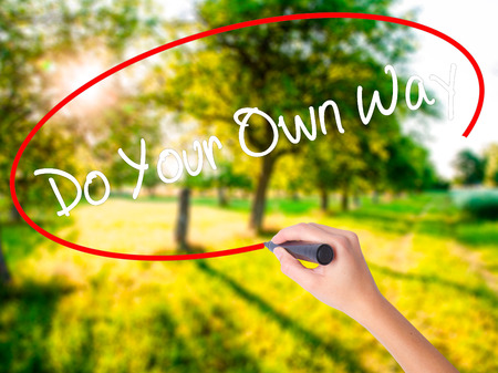 Woman Hand Writing Do Your Own Way  on blank transparent board with a marker isolated over green field background. Stock Photo Stock Photo