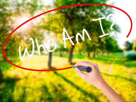 self awareness: Woman Hand Writing Who Am I? on blank transparent board with a marker isolated over green field background. Business concept. Stock Photo