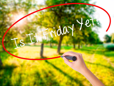 tiredness: Woman Hand Writing Is It Friday Yet? on blank transparent board with a marker isolated over green field background. Stock Photo