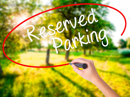 Woman Hand Writing Reserved Parking on blank transparent board with a marker isolated over green field background. Business concept. Stock Photo