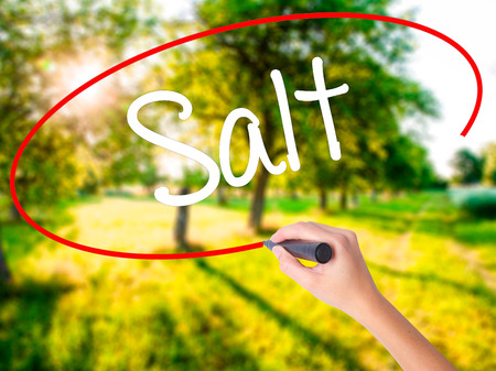 Woman Hand Writing Salt on blank transparent board with a marker isolated over green field background. Stock Photo