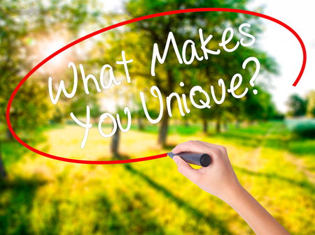 Woman Hand Writing What Makes You Unique? on blank transparent board with a marker isolated over green field background. Business concept. Stock Photo