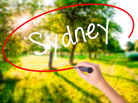 Woman Hand Writing Sydney  on blank transparent board with a marker isolated over green field background. Business concept. Stock Photo