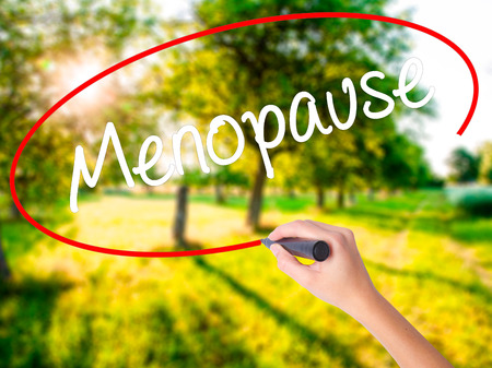 midlife: Woman Hand Writing Menopause on blank transparent board with a marker isolated over green field background. Stock Photo