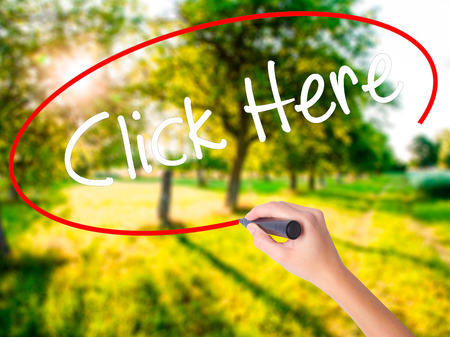 Woman Hand Writing Click Here on blank transparent board with a marker isolated over green field background. Business concept. Stock Photo