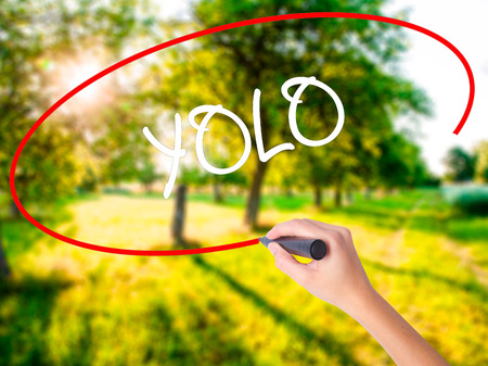 Woman Hand Writing YOLO (You Only Live Once) on blank transparent board with a marker isolated over green field background. Business concept. Stock Photo