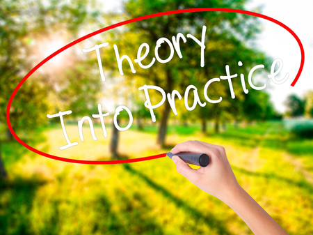 Woman Hand Writing Theory Into Practice on blank transparent board with a marker isolated over green field background. Business concept. Stock Photo Stock Photo