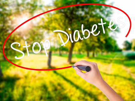 Woman Hand Writing Stop Diabetes on blank transparent board with a marker isolated over green field background. Business concept. Stock Photo Stock Photo