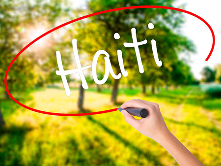 princes street: Woman Hand Writing Haiti on blank transparent board with a marker isolated over green field background. Business concept. Stock Photo