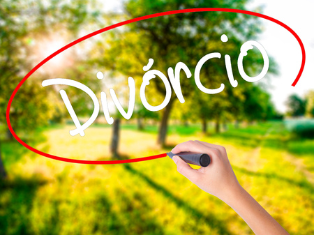 Woman Hand Writing Divorcio (Divorce in Portuguese) on blank transparent board with a marker isolated over green field background. Stock Photo