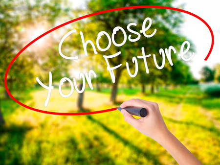 Woman Hand Writing Choose your Future on blank transparent board with a marker isolated over green field background. Business concept. Stock Photo Imagens