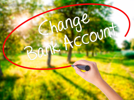 Woman Hand Writing Change Bank Account on blank transparent board with a marker isolated over green field background. Stock Photo