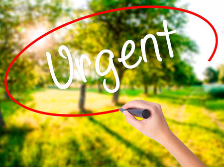 Woman Hand Writing Urgent  with a marker over transparent board . Isolated on background. Business, technology, internet concept. Stock  Photo Stock Photo