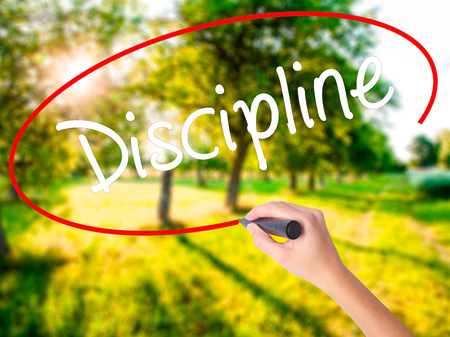 disciplined: Woman Hand Writing Discipline on blank transparent board with a marker isolated over green field background. Business concept. Stock Photo