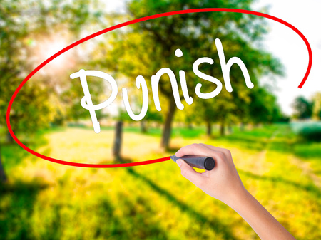 discouraging: Woman Hand Writing Punish on blank transparent board with a marker isolated over green field background. Stock Photo