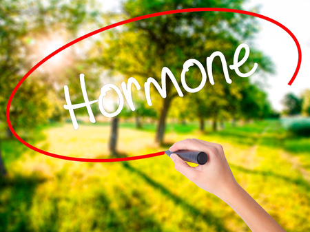 Woman Hand Writing Hormone on blank transparent board with a marker isolated over green field background. Stock Photo