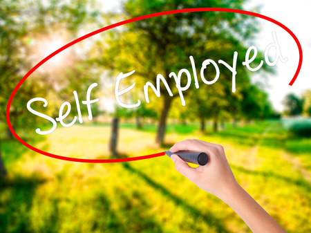 Woman Hand Writing Self Employed on blank transparent board with a marker isolated over green field background. Business concept. Stock Photo