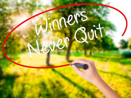 Woman Hand Writing Winners Never Quit on blank transparent board with a marker isolated over green field background. Stock Photo