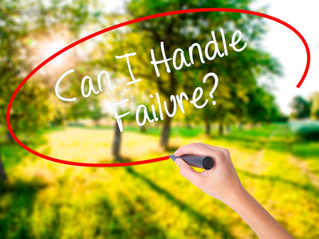 Woman Hand Writing Can I Handle Failure? on blank transparent board with a marker isolated over green field background. Business concept. Stock Photo Stock Photo