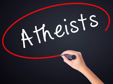 atheism: Woman Hand Writing Atheists on blank transparent board with a marker isolated over black background. Business concept. Stock Photo Stock Photo