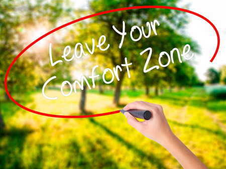 Woman Hand Writing Leave Your Comfort Zone on blank transparent board with a marker isolated over green field background. Business concept. Stock Photo