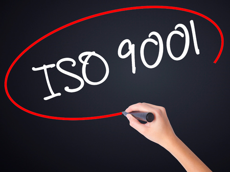 Woman Hand Writing  Iso 9001 on blank transparent board with a marker isolated over black background. Business concept. Stock Photo