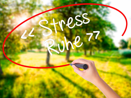 Woman Hand Writing Stress Ruhe  (Stress - Peacein German) on blank transparent board with a marker isolated over green field background. Stock Photo