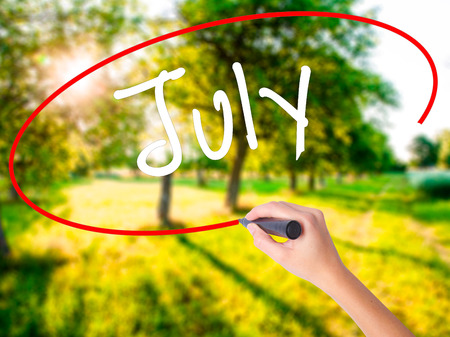 Woman Hand Writing July on blank transparent board with a marker isolated over green field background. Business concept. Stock Photo