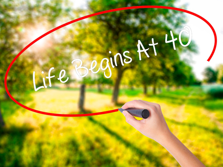 Woman Hand Writing Life Begins At 40  on blank transparent board with a marker isolated over green field background. Business concept. Stock Photo Stock Photo