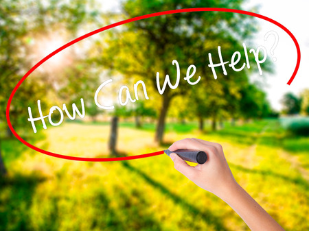 can we help: Woman Hand Writing How Can We Help? on blank transparent board with a marker isolated over green field background. Stock Photo